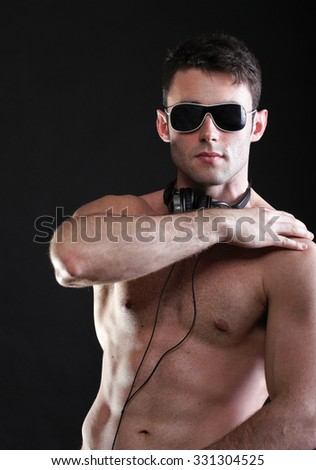 handsome man listening to music on headphone black background