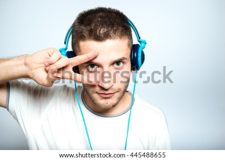 handsome man listening to music on headphones, conference, Skype, isolated on a gray background