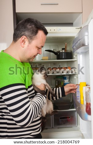 Handsome man looking for something for cat in refrigerator   - stock photo