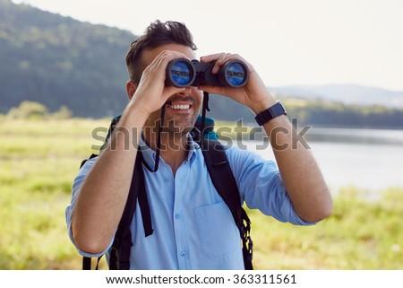 Handsome man looking through binoculars during hiking adventure - stock photo