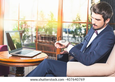 Handsome man looking time at watch. Waiting and sitting at cafe or restaurant. Businessman dressed in fashion costume. Stylish man. Laptop - stock photo