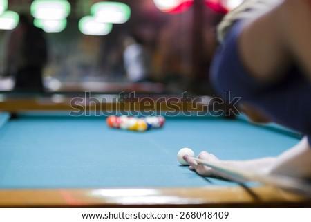 Handsome man looking to break the balls in billiard - stock photo