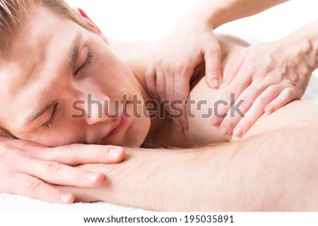 Handsome man lying in a spa salon enjoying a deep tissue back massage. - stock photo