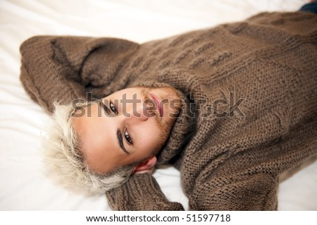 Handsome man lying in bed relaxing - stock photo