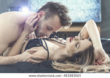 Handsome man lying in bed with a beautiful young woman