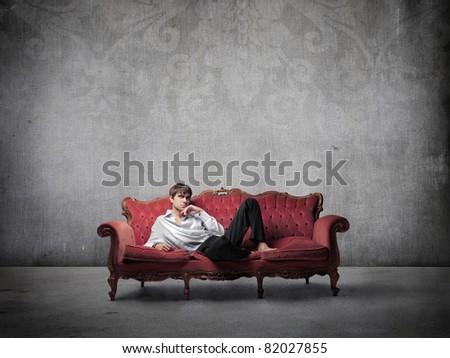 Handsome man lying on a sofa - stock photo
