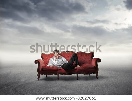 Handsome man lying on a sofa in a desert - stock photo