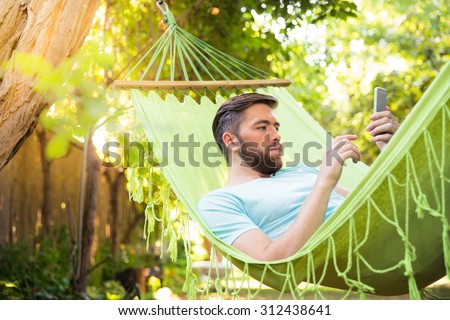 Handsome man lying on hammok and using smartphone outdoors  - stock photo