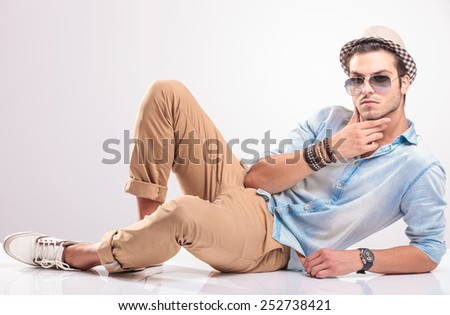 Handsome man lying on the floor, holding his hand to his chin, thinking. - stock photo