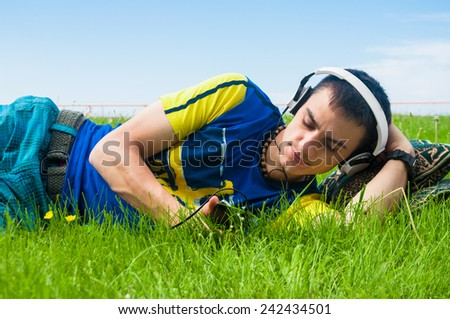 handsome man lying on the grass and listening the music - stock photo