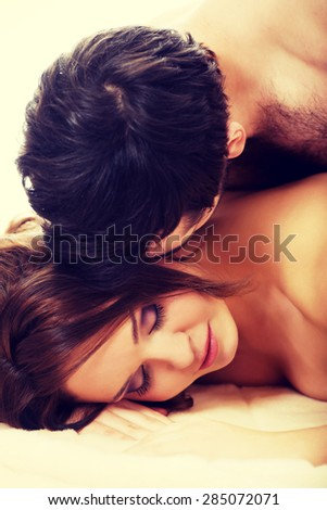Handsome man lying on woman in bed. - stock photo