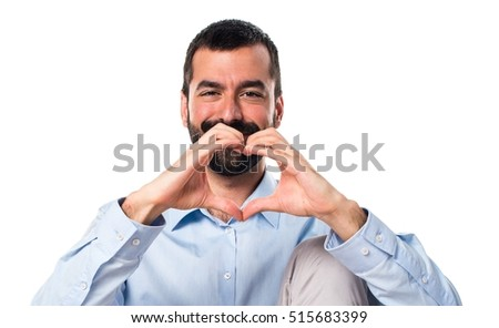 Handsome man making a heart with his hands