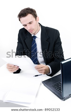Handsome man, male model as businessman, boss, manager, executive director in suit reading correspondence in office near computer, made in studio on white background - stock photo