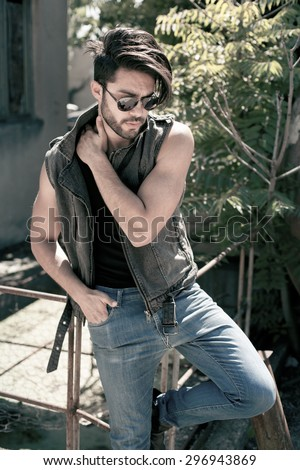 handsome man model dressed punk, hipster posing dramatic in grunge location