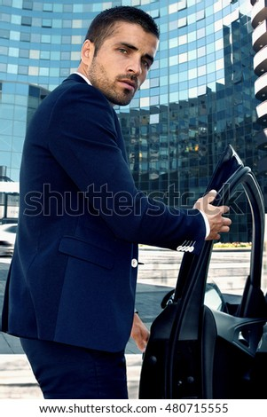 handsome man near the car on a background of cityscape