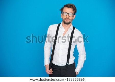 handsome man on blue wearing white shirt and braces on blue with glasses - stock photo