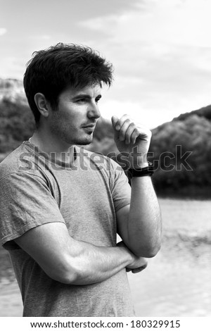 handsome man on summer vacation relaxing at the lake thinking in black and white style - stock photo
