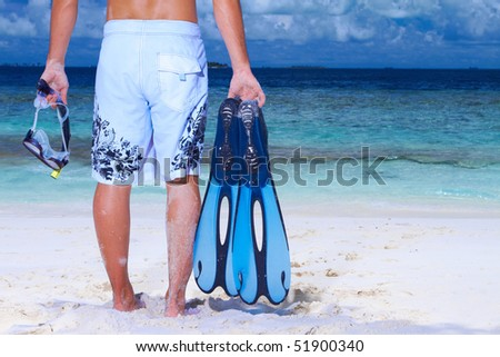 Handsome man on the beach holding fin and pipe