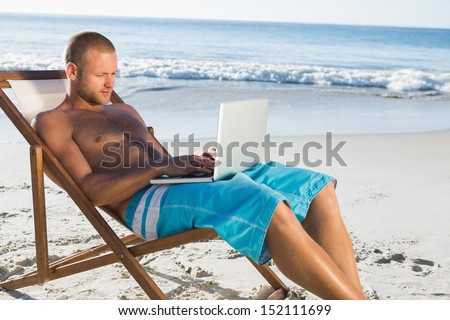 Handsome man on the beach using his laptop while relaxing on his deck chair