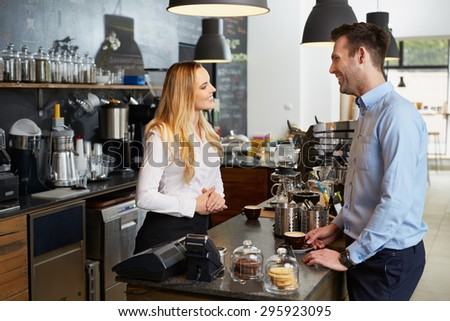 Handsome man orders coffee at cafe. Small business - coffee shop - stock photo