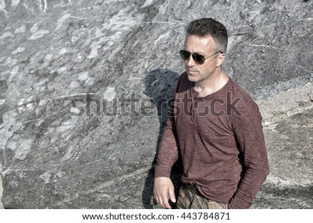 Handsome man over stones view. Outdoor male portrait, image toned. - stock photo
