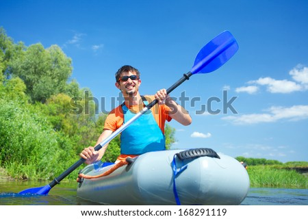 Handsome man paddling a kayak on the river, enjoying a lovely summer day - stock photo