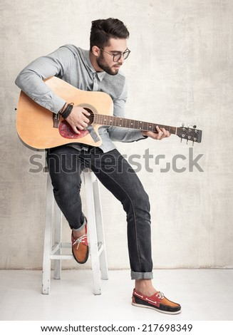 handsome man playing an acoustic guitar against grunge wall - stock photo