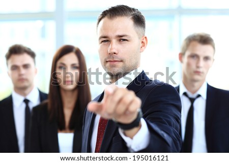 Handsome man pointing his finger at you on the background of business people  - stock photo