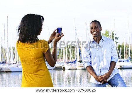 Handsome man posing for vacation photo at harbor with sailboats - stock photo
