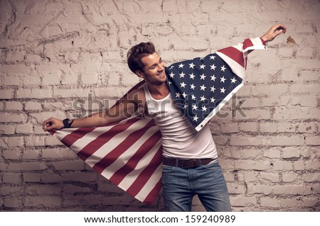 Handsome man posing with American flag. Smile and using flag like cloak  - stock photo