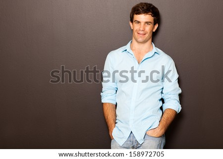 handsome man posing with hands in pockets on black - stock photo