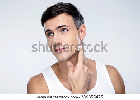 Handsome man putting on cream lotion on face - stock photo