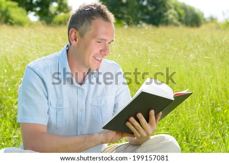 Handsome man reading book outside