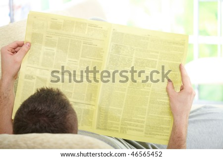 Handsome man reading newspaper, laying on couch at home - stock photo