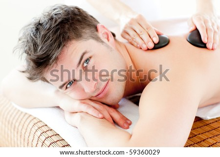 Handsome man receiving a back massage with hot stone in a spa center - stock photo
