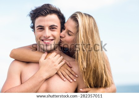 Handsome man receiving kiss from his gilfriend at the beach - stock photo
