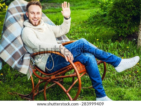 Handsome man relax in rocking-chair with plaid in a summer garden.  - stock photo