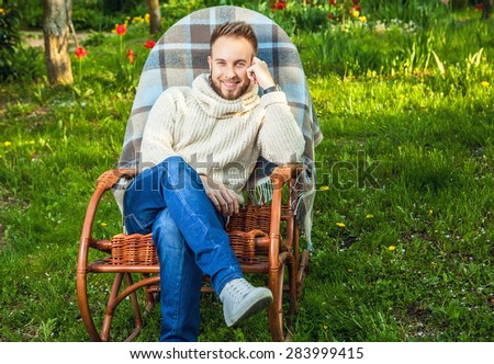 Handsome man relax in rocking-chair with plaid & phone in a summer garden.  - stock photo