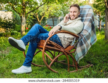 Handsome man relax in rocking-chair with plaid & phone in a summer garden.