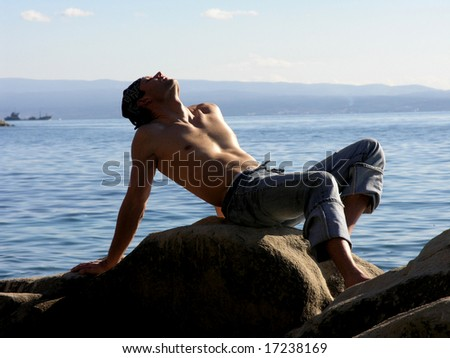 Handsome man relaxing  at the rocky beach - stock photo