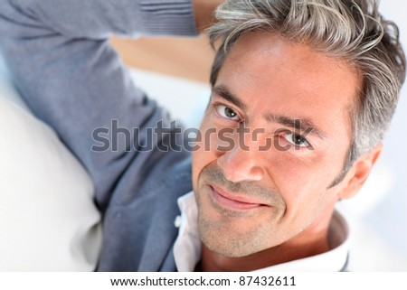 Handsome man relaxing in sofa at home - stock photo