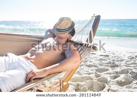 Handsome man resting in the hammock at the beach - stock photo