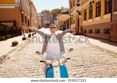 Handsome man riding a motorbike picking up both hands - stock photo