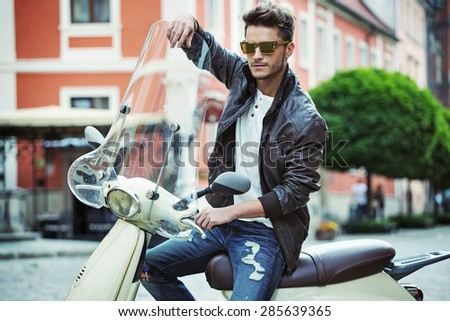 Handsome man riding a vintage scooter - stock photo