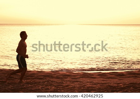 Handsome man running on the sunset sandy beach, selective focus
