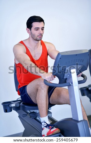 Handsome man running on the treadmill in modern gym - stock photo