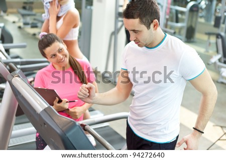 handsome man running on  treadmill  with personal trainer - stock photo