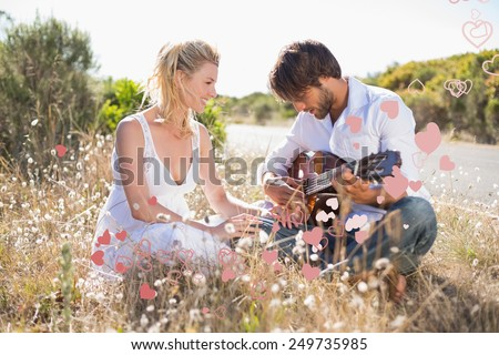 Handsome man serenading his girlfriend with guitar against valentines heart design - stock photo