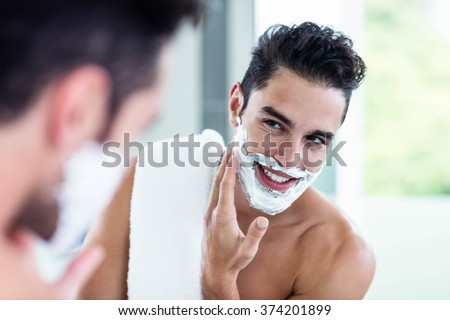 Handsome man shaving his beard in bathroom - stock photo