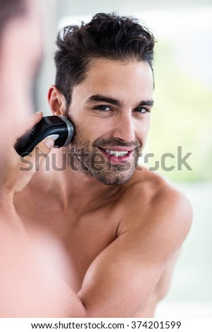 Handsome man shaving in the mirror in the bathroom